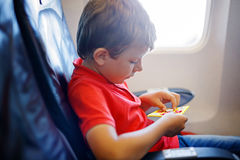 Little kid boy playing tic tac toe game during flight on airplane. Stock Photos