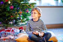 Little kid boy playing video game console on Christmas Stock Photos