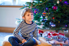 Little kid boy playing video game console on Christmas Stock Images