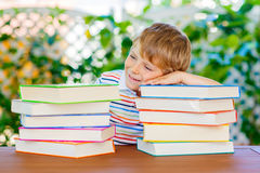 Little kid boy reading book at school Stock Images