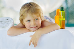Little kid boy relaxing in spa with enjoying massage Stock Photos