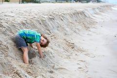 Little kid boy running on the beach of ocean royalty free stock image