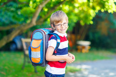 Little kid boy with school satchel on first day to school. Beautiful happy little kid boy with glasses and backpack or satchel on his first day to school or Stock Photos
