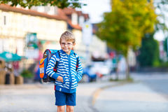 Little kid boy with school satchel on first day to school. Beautiful happy little kid boy with glasses and backpack or satchel on his first day to school or Stock Photo