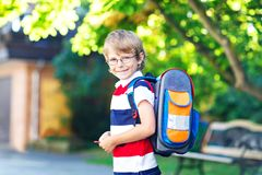 Little kid boy with school satchel on first day to school. Happy little kid boy with glasses and backpack or satchel on his first day to school or nursery. Child Royalty Free Stock Images