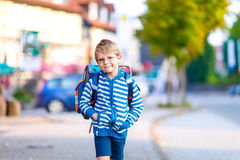 Little kid boy with school satchel on first day to school. Beautiful happy little kid boy with glasses and backpack or satchel on his first day to school or Royalty Free Stock Photo