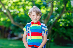 Little kid boy with school satchel on first day to school. Happy little kid boy in colorful shirt and backpack or satchel on his first day to school or nursery Royalty Free Stock Photography