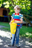 Little kid boy with school satchel on first day to school. Happy little kid boy in colorful shirt and backpack or satchel and traditional German school bag Stock Photos