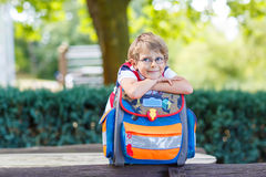 Little kid boy with school satchel on first day to school. Happy little kid boy with glasses and backpack or satchel on his first day to school . Child outdoors Royalty Free Stock Photography