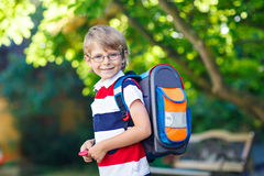 Little kid boy with school satchel on first day to school. Happy little kid boy with glasses and backpack or satchel on his first day to school or nursery. Child Stock Photography