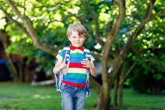 Little kid boy with school satchel on first day to school. Happy little kid boy in colorful shirt and backpack or satchel on his first day to school or nursery Stock Photo