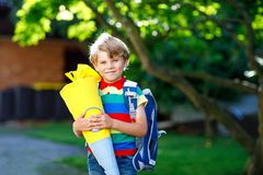 Little kid boy with school satchel on first day to school, holding school cone with gifts Royalty Free Stock Photos