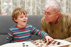 Little kid boy and senior grandfather playing together checkers game. Cute little kid boy and senior grandfather playing together checkers game. Grandchild and stock images