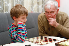 Little kid boy and senior grandfather playing together checkers game. Cute little kid boy and senior grandfather playing together checkers game. Grandchild and stock photography