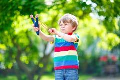Little kid boy shooting wooden slingshot Stock Photography