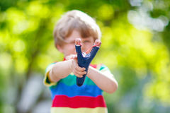 Little kid boy shooting wooden slingshot Stock Photography