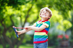 Little kid boy shooting wooden slingshot Royalty Free Stock Photo