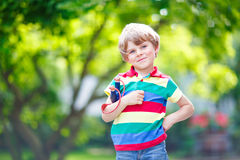 Little kid boy shooting wooden slingshot Stock Photos