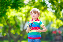 Little kid boy shooting wooden slingshot Royalty Free Stock Photography