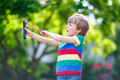 Little kid boy shooting wooden slingshot Royalty Free Stock Images