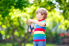Little kid boy shooting wooden slingshot Stock Images