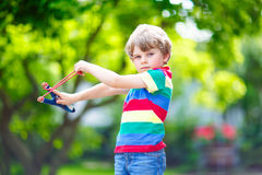 Little kid boy shooting wooden slingshot Stock Photos