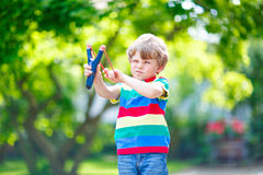 Little kid boy shooting wooden slingshot Royalty Free Stock Image