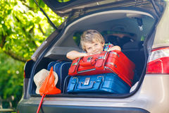 Little kid boy sitting in car trunk just before leaving for vaca Stock Photo