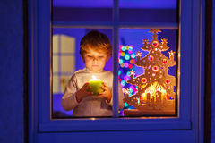 Little kid boy standing by window at Christmas time and holding Royalty Free Stock Photography