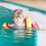 Little kid boy with swimmies learning to swim in Stock Photo