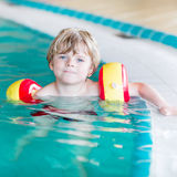 Little kid boy with swimmies learning to swim in an indoor pool. Active little toddler child, cute boy with water wings learning to swim in an indoor pool Royalty Free Stock Photo