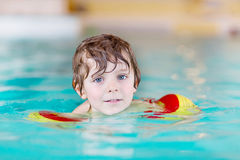 Little kid boy with swimmies learning to swim in an indoor pool Stock Images