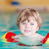 Little kid boy with swimmies learning to swim in an indoor pool Royalty Free Stock Images