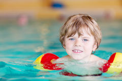Little kid boy with swimmies learning to swim in an indoor pool Stock Image