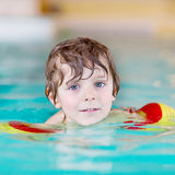 Little kid boy with swimmies learning to swim in an indoor pool Royalty Free Stock Photo