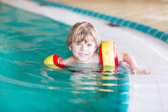 Little kid boy with swimmies learning to swim in an indoor pool Royalty Free Stock Photography