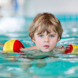 Little kid boy with swimmies learning to swim in an indoor pool Stock Photography