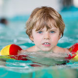 Little kid boy with swimmies learning to swim in an indoor pool Royalty Free Stock Photos