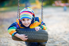 Little kid boy swinging on playground outdoors Royalty Free Stock Images