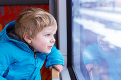 Little kid boy traveling and looking out train window outside. Little kid boy looking out train window outside, while it moving. Going on vacations and traveling Stock Photography