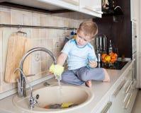 Little kid boy washing dish on kitchen stock image
