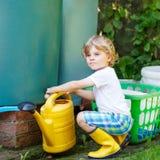 Little kid boy watering plants in garden in summer Stock Photography