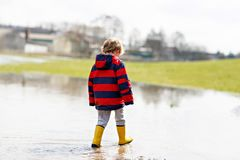 Little kid boy wearing yellow rain boots and walking and jumping into puddle on warm sunny spring day. Happy child in. Colorful fashion casual rain clothes stock photo