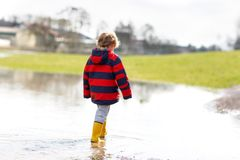Little kid boy wearing yellow rain boots and walking and jumping into puddle on warm sunny spring day. Happy child in. Colorful fashion casual rain clothes royalty free stock images