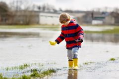 Little kid boy wearing yellow rain boots and walking and jumping into puddle on warm sunny spring day. Happy child in. Happy little kid boy in yellow rain boots stock photo