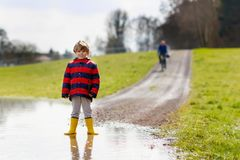 Little kid boy wearing yellow rain boots and walking and jumping into puddle on warm sunny spring day. Happy child in colorful fashion casual rain clothes Stock Photos