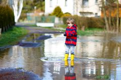 Little kid boy wearing yellow rain boots and walking and jumping into puddle on warm sunny spring day. Happy child in colorful fashion casual rain clothes Stock Image