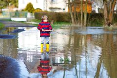 Little kid boy wearing yellow rain boots and walking and jumping into puddle on warm sunny spring day. Happy child in colorful fashion casual rain clothes Royalty Free Stock Photo