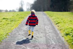 Little kid boy wearing yellow rain boots and walking on nature path on warm sunny spring day. Happy child in colorful fashion casual rain clothes having fun Royalty Free Stock Image