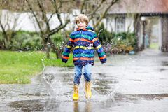 Little kid boy wearing yellow rain boots and walking during sleet, rain and snow on cold day. Child in colorful fashion casual clothes jumping in a puddle Royalty Free Stock Image